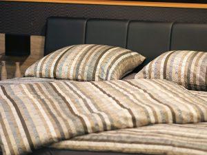 Bei einer Hausstaubmilbenallergie stören Milben den ruhigen Schlaf.